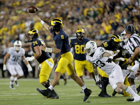 Michigan QB John O'Korn scrambles away from Michigan State LB Chris Frey in the first half at Michigan Stadium in Ann Arbor on Sat., Oct. 7, 2017.