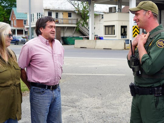 Brian and Jean DuMoulin chat with an U.S. Border Patrol agent outside their home that sits across the U.S.-Canadian Border. The Canadian border post is across the street. The Border Patrol agent came out to see why the DuMoulins were taking photos of the border posts and their house.