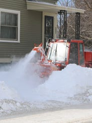 "A blower-equipped sidewalk plow, or ""Snow Dragon,"""