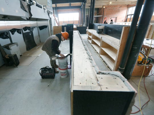 Joel Thompson of Rochester with Olver Drywall Inc. works in the space that will become Nosh restaurant in the Neighborhood of the Arts.