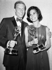 This May 25, 1964 file photo shows Dick Van Dyke, left, and Mary Tyler Moore, co-stars of 'The Dick Van Dyke Show' backstage at the Palladium with their Emmys for best actor and actress in a series