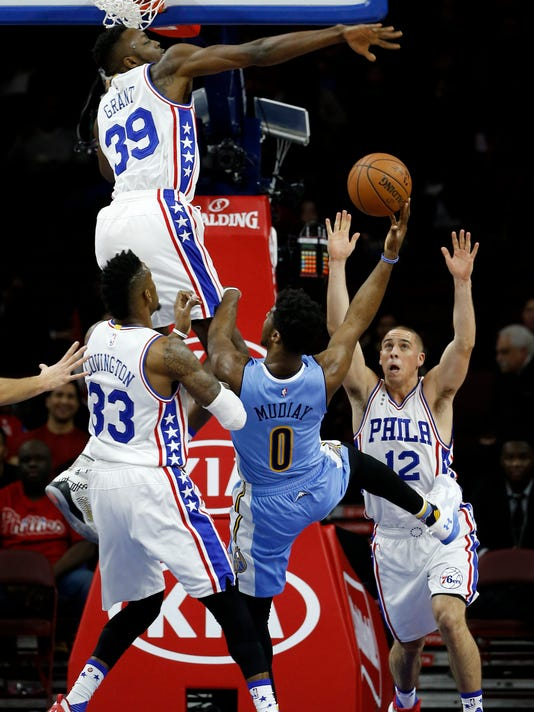 Denver Nuggets' Emmanuel Mudiay (0) goes up for a shot against Philadelphia 76ers' Jerami Grant (39) , T.J. McConnell (12) and Robert Covington (33) during the first half of an NBA basketball game, Saturday, Dec. 5, 2015, in Philadelphia. (AP Photo/Matt Slocum)