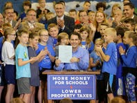 Gov. Scott Walker signs $76B Wisconsin budget with money for schools, fees for hybrids