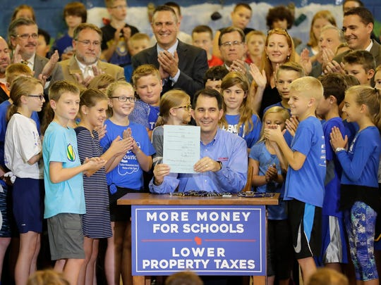 Gov. Walker poses with Neenah student after signing the two-year budget Thursday.