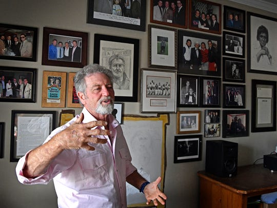 Larry Gatlin stands is front of a wall that contains