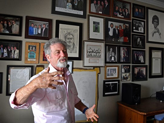 Larry Gatlin stands is front of a wall that contains photos of himself with many of country music's greatest artists Tuesday, June 26, 2018, in Nashville.