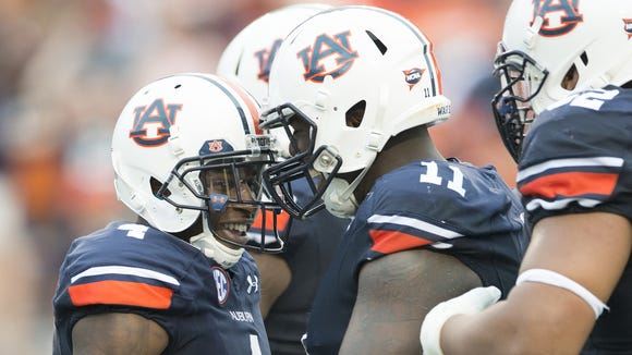 Auburn wide receiver Quan Bray (4) celebrates with Auburn defensive back Markell Boston (11) and Auburn offensive lineman Chad Slade (62) after returning a punt for a touchdown during the NCAA football game between Auburn and Louisiana Tech on Saturday, Sept. 27, 2014 in Auburn, Ala. Auburn defeated Louisiana Tech 45-17.