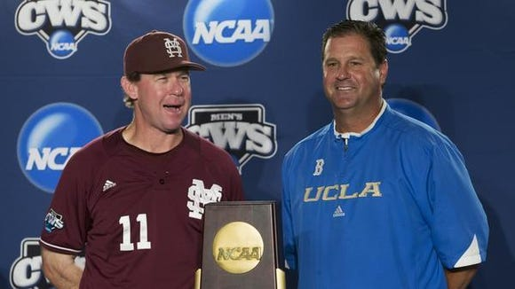 Mississippi State coach John Cohen, left, and UCLA coach John Savage pose with the College World Series trophy before the start of their national championship series in 2013.