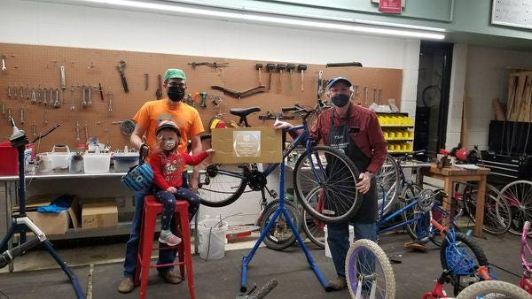 Tim Marchand, shop manager for the Topeka Community Cycle Project, on the right, displayed an award TCCP received while posing with Andy Fry, president of the board for TCCP, and Fry's daughter, Ava Fry.
