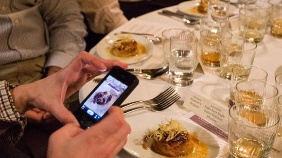 At the Columbus Inn for the MidAtlantic Food + Wine Festival in 2013, an attendee takes a photo of his upside-down apple, cheddar and bacon tart  paired with Blanton's original bourbon in 2013.