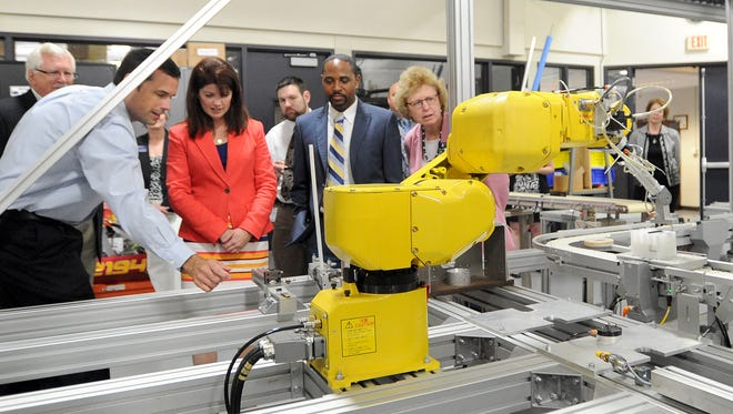 Lt. Governor Rebecca Kleefisch and Department of Workforce Development Secretary Reggie Newson get a view of a robotic arm at work inside Moraine Park Technical College. They were at the facillity to announce a grant to the school from the Wisconsin Fast Forward; Blueprint for Prosperity initiative.  Wednesday,  July 23, 2014. Doug Raflik/Action Reporter Media
