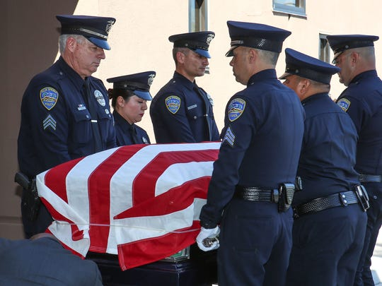 Palm Springs police officers carry the body of Gil Vega into the Palm Springs Convention Center for services for the two fallen officers, October 18, 2016.
