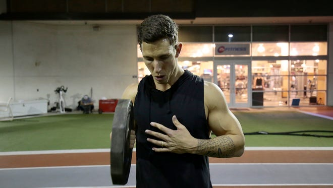 Cincinnati Reds relief pitcher Michael Lorenzen curls with his throwing arm during his first weights session before Spring Training at the 24 Hour Fitness in La Jolla, Calif., on Saturday, Jan. 14, 2017. Lorenzen, recognizable in past seasons for his body builder-like physique, decided to cut weight and mass for 2017.