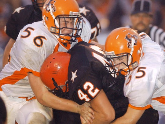 New Lexington linebackers Paul Fain (55) and Josh Conrad (56) tackle Crooksville's Jake Danison during the Panthers' 9-0 win in 2005 at Village Park. The Ceramics and Panthers, separated by just seven miles, have been playing for more than 70 years.