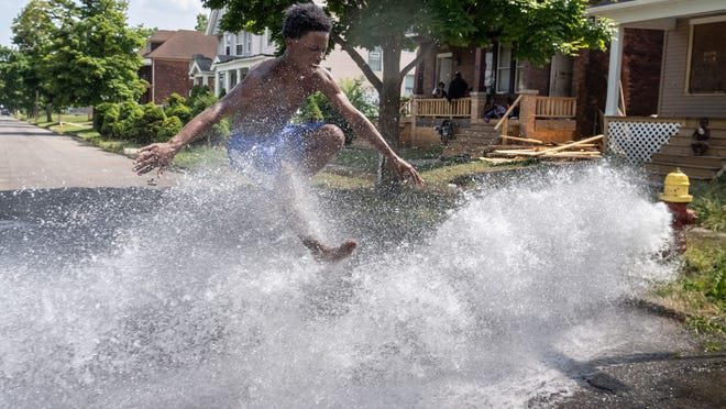 Michael Greer of Detroit jumps over water flowing from an open hydrant on Townsend  Street in Detroit's Islandview neighborhood on Tuesday, July 7, 2020 as the family cools off from the heat wave in the running water.