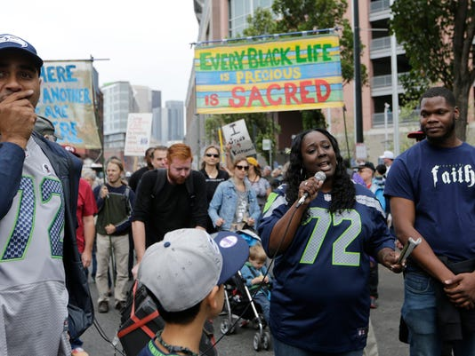 Katrina Johnson, second from right, speaks outside CenturyLink Field after a taking part in a march supporting Black Lives Matter and other social causes before an NFL football game between the Seattle Seahawks and the San Francisco 49ers, Sunday, Sept. 17, 2017, in Seattle. Johnson is wearing the #72 jersey of Seahawks defensive end Michael Bennett, who has been a vocal supporter of various social issues, and who reached out to her family after Johnson's cousin, Charleena Lyles, was fatally shot by Seattle Police earlier in the year. (AP Photo/John Froschauer)