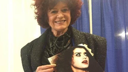 """Patricia Quinn, who played Magenta in """"The Rocky Horror Picture Show,"""" poses with a photo of herself as the character. She flew in from London for the event."""