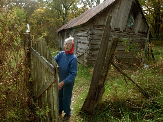 """I'm just an ordinary person,"" said Birdle Mannon in this photo taken Dec. 5, 1997. Birdle stands in the gate of her modest cabin in southwest Missouri, her home since 1916. She lives in a world less bullied by technology, with no electicity, no furnace, no bathroom, no running water, no television and no washing machine. Photo made 12/5/97"