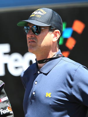 Michigan football coach Jim Harbaugh stands on pit road during the NASCAR Sprint Cup Series FireKeepers Casino 400 at Michigan International Speedway on June 12, 2016, in Brooklyn.