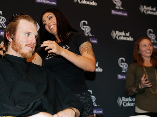 Colorado Rockies starting pitcher Jon Gray, left, listens as his long locks are trimmed by stylist Megan Duran as Gray's wife, Jacklyn, talks about her husband's donation of his hair to Locks For Love, a non-profit organization that provides hairpieces to financially disadvantaged children on Tuesday, April 11, 2017, in Denver. Gray has not cut his hair for more than two years before Tuesday's trim. (AP Photo/David Zalubowski)