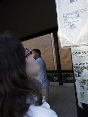 Angela Pancella looks at articles from the 2001 riots in Cincinnati before a moment of silence.