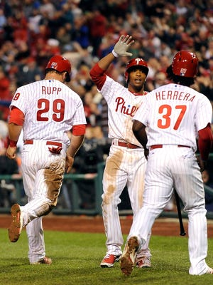 The Phillies' Ben Revere (center) celebrates with Cameron Rupp (left) and Odubel Herrera after they score on a Cesar Hernandez single to right field in the seventh inning Friday against the Washington Nationals in Philadelphia. The Phillies won 4-1.