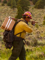 A firefighter walks along a section of Highway 143