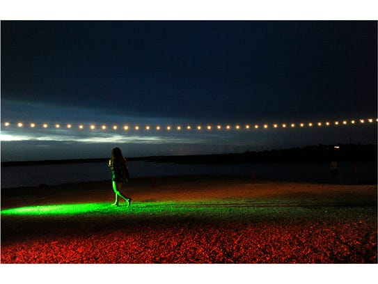 A woman steps into a momentary pool of light at Fisher