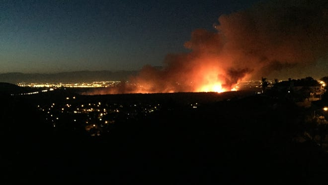 A brush fire that broke out Saturday evening, April 18, 2015 burns in the Dam Prado Dam Flood Control Basin north of the city of Corona, Calif.