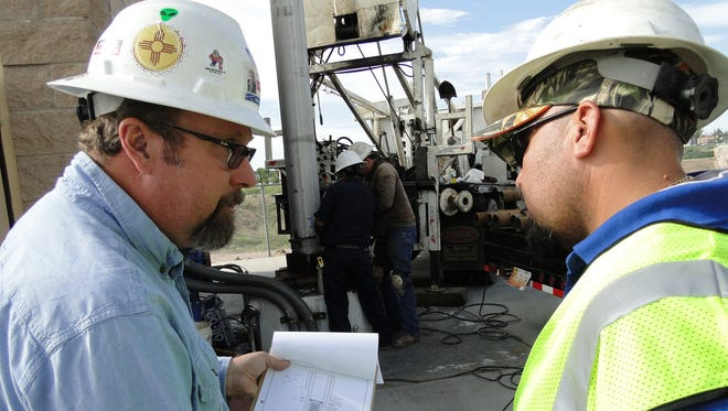 Marco Wikstrom, hydrogeologist with John Shomaker and Associates, compares notes with Paul Gamboa, senior water production operator, at the rehab of Well No. 67.