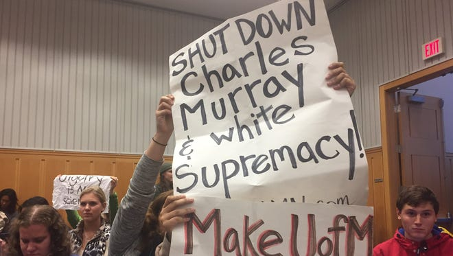 Some attending the presentation by author Charles Murray at U-M Wednesday night held up signs denouncing his presence and books.