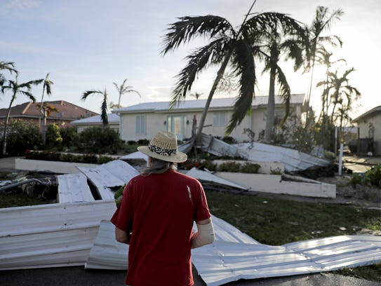 A roof is strewn across a home's lawn as Rick Freedman