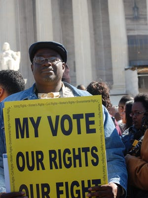 Ray Heard from Alabama holds up a sign during a rally outside the U.S. Supreme Court in Washington on Wednesday, Feb. 27, 2013. Inside, the court heard arguments in a voting rights case - Shelby v. Holder that challenges a key provision of the 1965 Voting Rights Act.