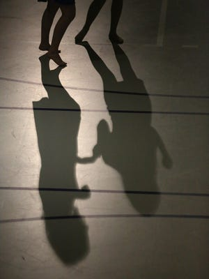 Two girls cast long shadows as they dance. The fifth annual Big Band Dance was held Feb. 24 at Blake Fieldhouse in Indianola featuring the Indianola Middle School Jazz Band, the Indianola High School Jazz 1 and Jazz 2 bands and the Indianola Community Jazz Ensemble.
