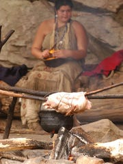 Nicole Martin plays the role of a 17th-century Wampanoag woman preparing a meal in an outdoor cooking area at Plimoth Plantation near Plymouth, Massachusetts.