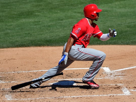 FILE - In this March 11, 2017, file photo, Los Angeles Angels' Ben Revere follows through on an RBI base hit against the Los Angeles Dodgers during the third inning of a spring training baseball game, in Phoenix. Revere signed a minor-league deal with the Reds, Monday, Feb. 26, 2018, who need depth in the outfield and an upgrade on the bench. (AP Photo/Matt York, File)