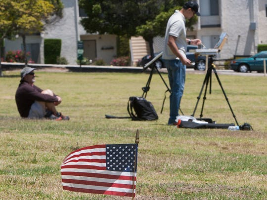An American flag marks the grave of Oliver Rupert Logue, U.S. military veteran, in Cemetery Memorial Park in Ventura as regular outdoor activity continues.
