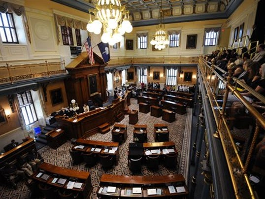 The desk of S.C. Sen. Clementa Pinckney is draped in black cloth with a single rose and vase in an empty chamber prior to a Senate session, Thursday, June 18, 2015, at the Statehouse in Columbia, S.C.  State Sen. Clementa Pinckney was one of those killed Wednesday night in a shooting at the Emanuel AME Church in Charleston.  (AP Photo/Rainier Ehrhardt)