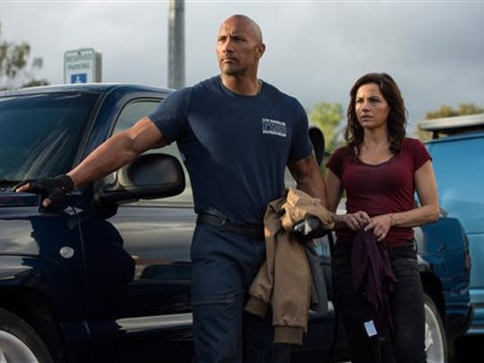"This photo provided by Warner Bros. Pictures shows Dwayne Johnson, left, as Ray, and Carla Gugino as Emma, in a scene from the action thriller, ""San Andreas."" The movie releases in theaters on May 29, 2015.  (Jasin Boland/Warner Bros. Pictures via AP)"