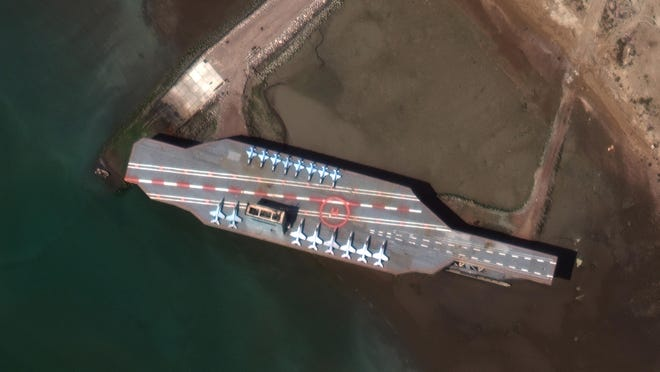 In this Feb. 15, 2020 satellite photo provided by Maxar Technologies, a mockup aircraft carrier built by Iran can be seen at Bandar Abbas, Iran, before being put to sea. Satellite photographs released Monday, July 27, 2020, showed Iran has moved the aircraft carrier out to sea likely for naval drills amid heightened tensions between Tehran and the U.S.