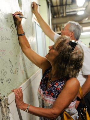 Eileen Holman Kron, class of 1977, and Mike Isakson, class of 1971, sign their name on the wall in the basement of Tech during a tour Friday, July 28. Signing the wall is a tradition of students who sneak into the old pool area.