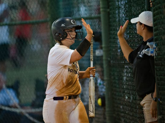 Prattville Christian's Kathryn Fallen high fives her coach after scoring during the AHSAA Class 3A Softball State Championship game between Prattville Christian and Geneva on Friday, May 18, 2018, in Montgomery, Ala.