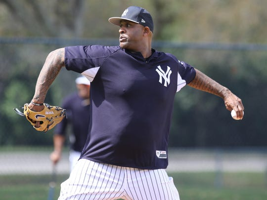 CC Sabathia pitches the ball as the pitchers practiced playing defense.