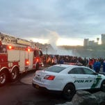 A crowd gathers near where a woman reportedly went over the American Falls in Niagara Falls, N.Y.