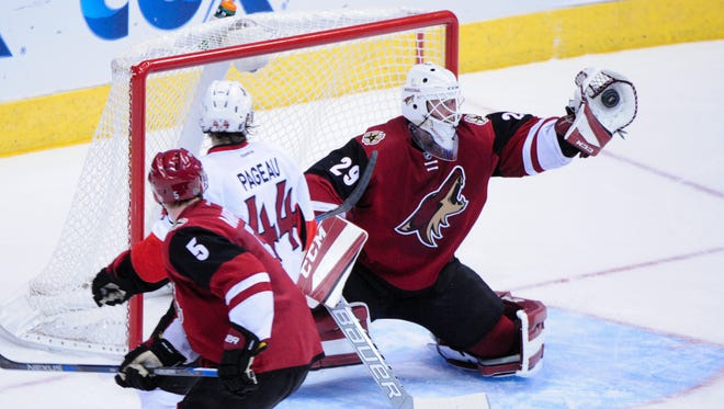 Nov 28, 2015: Arizona Coyotes goalie Anders Lindback (29) males a save as defenseman Connor Murphy (5) defends and Ottawa Senators center Jean-Gabriel Pageau (44) looks on during the third period at Gila River Arena.