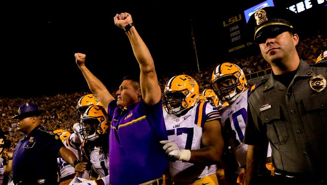 LSU Tigers head coach Ed Orgeron leads his team onto the field before the game against Alabama.