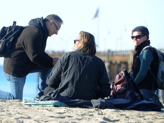 Homeless count volunteers Jim Duran, left, and Jennifer Shawn, right, speak with Shawn Heise near the Ventura Pier on Feb. 22, 2018, while counting the local homeless population.
