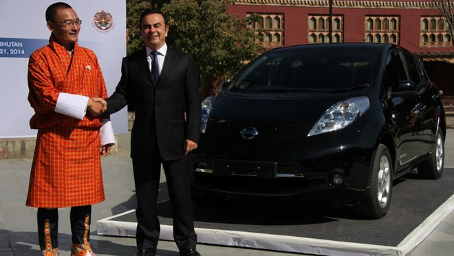 In this photo released by Nissan Motor Co., Bhutanese Prime Minister Tshering Tobgay, left, and Nissan President Carlos Ghosn pose for photos with the company's Leaf model in Thimphu, Bhutan