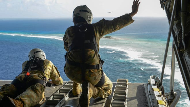 In this Dec. 8, 2015, file photo Cpl. Teome Matamua and Sgt. Phillip McIllvaney, Australian Army 176th Air Dispatch Squadron loadmasters, wave to islanders in the Federated States of Micronesia from the back of a C-130J Hercules after delivering donated goods and critical supplies to the islanders during Operation Christmas Drop.
