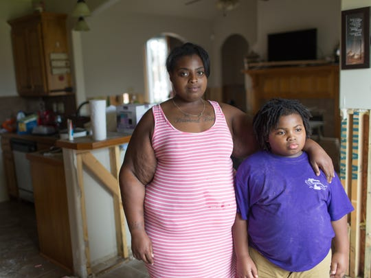 Marion Nora  and her 8-year-old son Gary Ross at their flood-damaged house in Lafayette August 25, 2016. They are spending nights at the Red Cross shelter at the Heymann Center.
